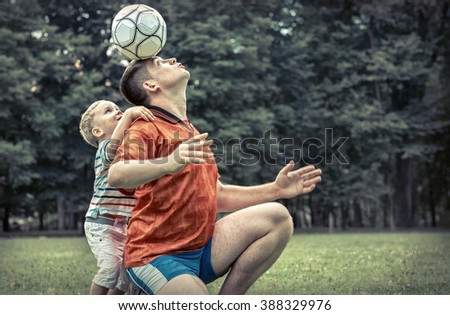 Father and son playing football in park at sunny day