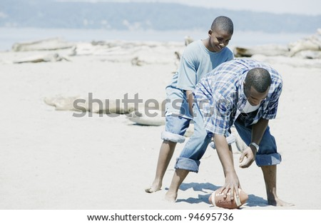 Father and son playing football on the beach - stock photo