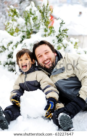 Father and son playing happily in snow making snowman, winter season - stock photo