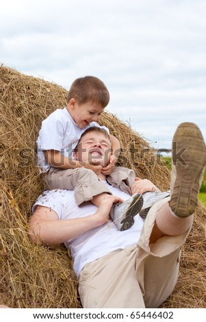 Father and son playing in haystack together - stock photo