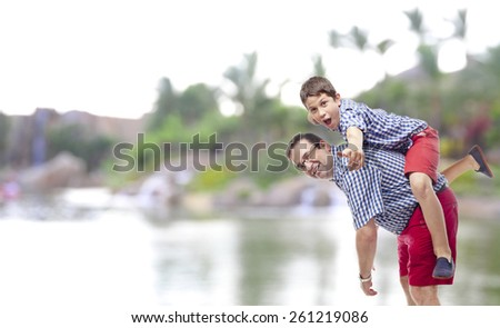 Father and son playing in the natural park - stock photo