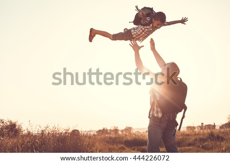 Father and son playing in the park at the sunset time. People having fun on the field. Concept of friendly family and of summer vacation. - stock photo