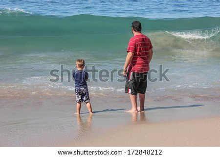 Father and son playing in the waves at the beach in Puerto Vallarta Mexico. with copy space  - stock photo