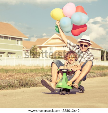 father and son playing near a house at the day time - stock photo