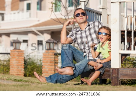 Father and son playing near the house at the day time. They sit in the white gazebo. Concept of friendly family. - stock photo