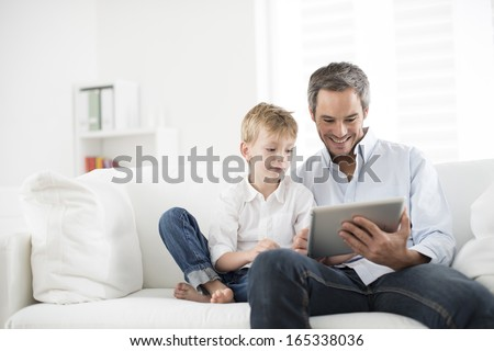 father and son playing on a tablet - stock photo