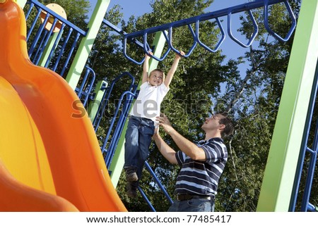 Father and son playing on monkey bars at the park - stock photo