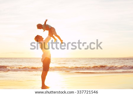Father and Son Playing on the Beach at Sunset - stock photo