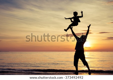 Father and son playing on the beach at the sunset time. Concept of friendly family.