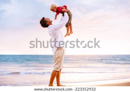 Father and Son Playing on the Beach by the Ocean - stock photo