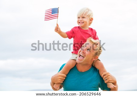 Father and son playing on the beach with American flag. USA celebrate 4th of July. - stock photo