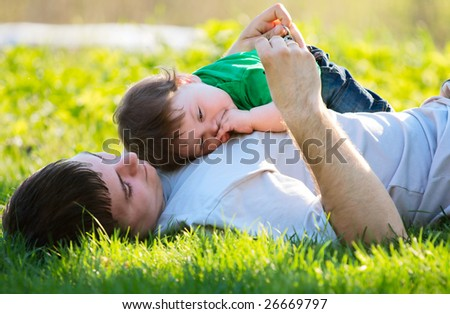 father and son playing on the grass - stock photo