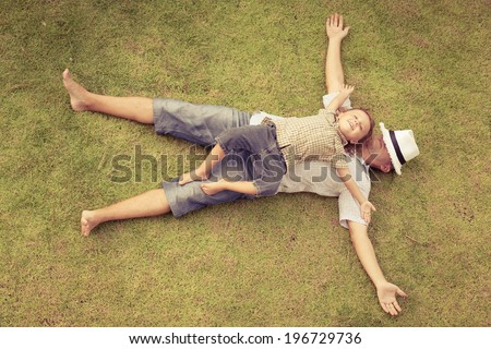 father and son playing on the grass at the day time - stock photo