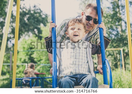 Father and son playing on the swing at the day time. Concept of friendly family.