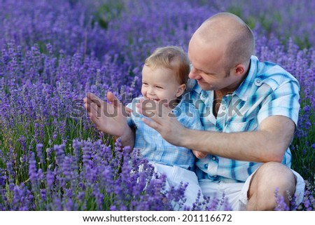 father and son playing pat-a-cake in the field - stock photo