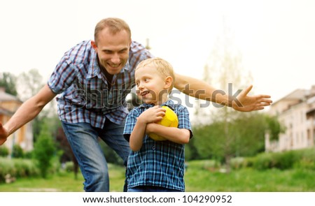 Father and son playing together at the park - stock photo