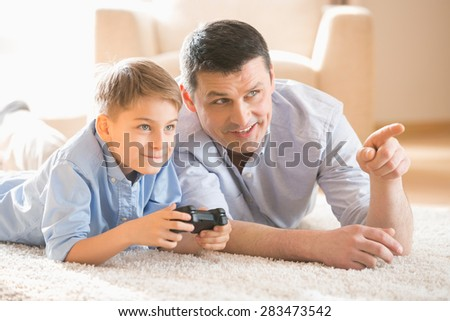 Father and son playing video game on floor at home