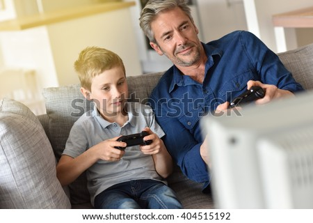 Father and son playing video game on tv