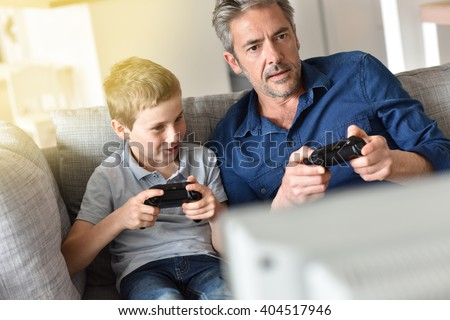 Father and son playing video game on tv - stock photo