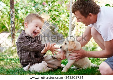 father and son playing with a labrador puppy in the garden. - stock photo