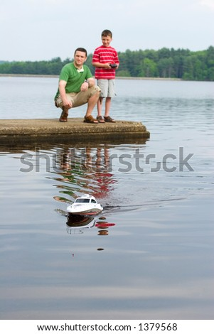 Father and son playing with a remote controlled boat - stock photo