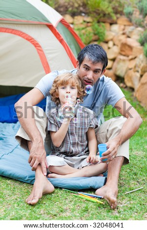 Father and son playing with bubbles in a tent