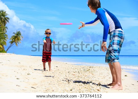 Father and son playing with flying disk at beach - stock photo