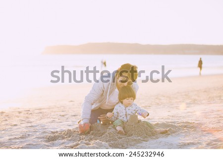 Father and son playing with sand on the beach, kissing and hugging.  - stock photo