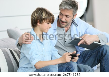 Father and son playing with smartphone - stock photo
