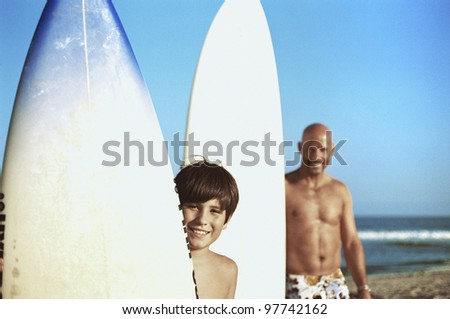 Father and son posing with surfboards - stock photo