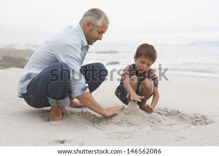 Father and son preparing sand castle together on beach - stock photo