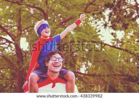 Father and son pretending to be superhero in park - stock photo