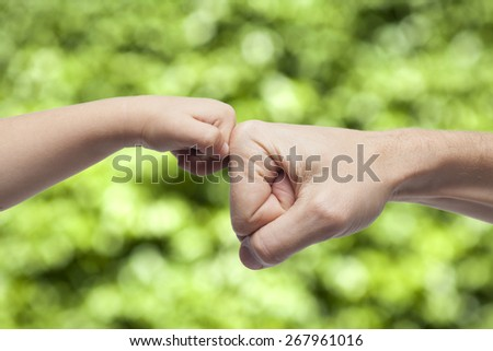 father and son punching fists/hands for agreement on green nature background