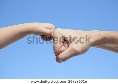 father and son punching for agreement on blue sky background