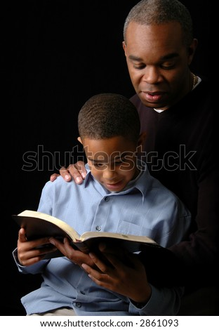 Father and son reading a Bible over a black background.