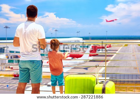 father and son ready for summer vacation, while waiting for boarding in international airport - stock photo