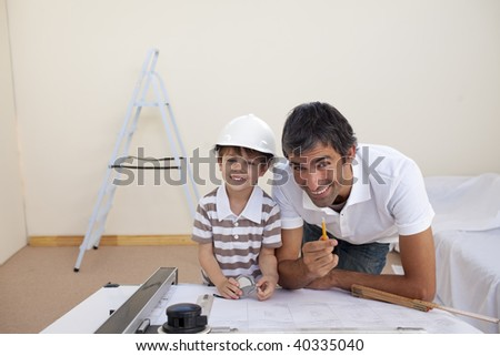Father and son refurbishing a bedroom at home - stock photo