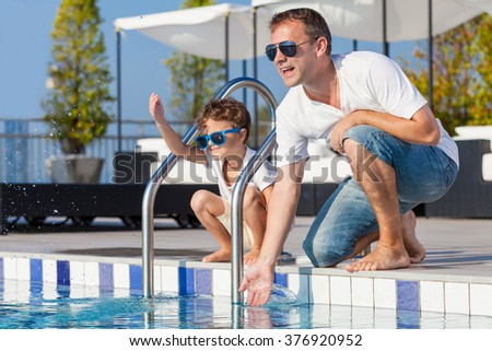 Father and son relaxing near a swimming pool  at the day time. Concept of friendly family. - stock photo