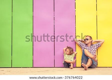 Father and son relaxing near the house at the day time. They sitting near are the colorful wall. Concept of friendly family. - stock photo
