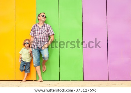 Father and son relaxing near the house at the day time. They standing near are the colorful wall. Concept of friendly family. - stock photo