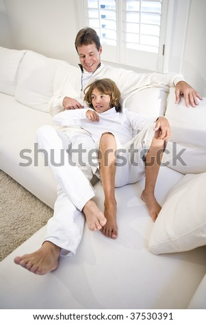 father and son relaxing on white sofa