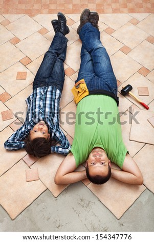 Father and son resting while laying ceramic floor tiles - stock photo