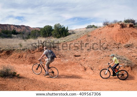 Father and son riding bikes on the trail. Palo Duro Canyon State Park, Texas, US - stock photo