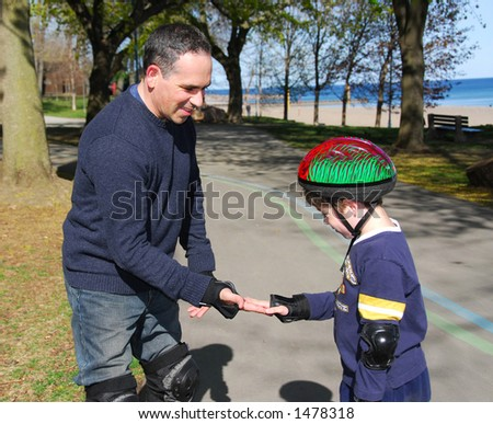 Father and son rollerblading together - stock photo