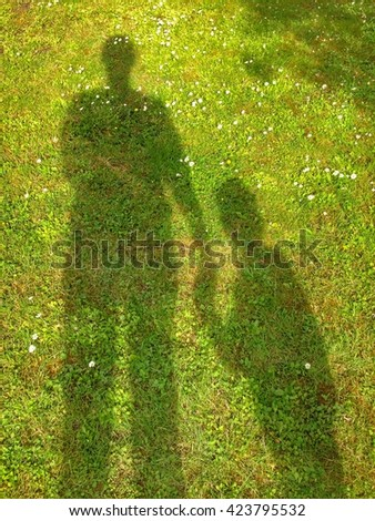 Father and son shadows giving hand on green grass background - stock photo