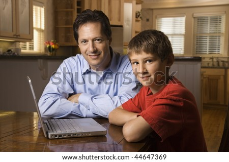 Father and son sitting at dining room table with wireless laptop computer. - stock photo