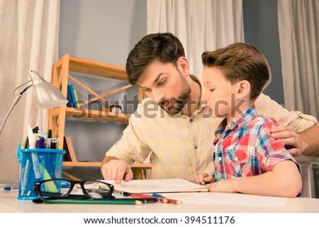 Father and son sitting at the table and reading interesting story - stock photo