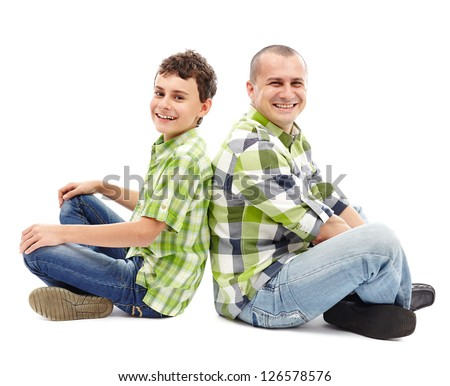 Father and son sitting back to back with crossed legs - stock photo