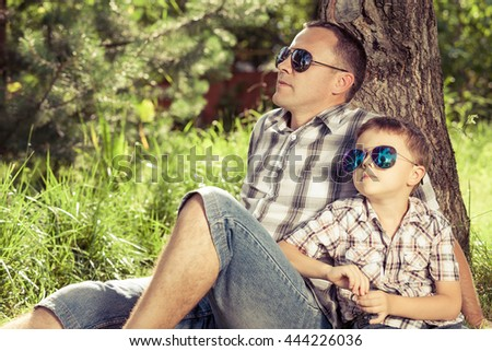 Father and son sitting near the tree in the garden at the day time. Family having fun on the nature. Concept of friendly family and of summer vacation.