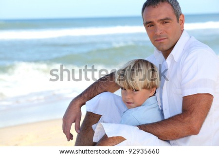 Father and son sitting on a beach - stock photo